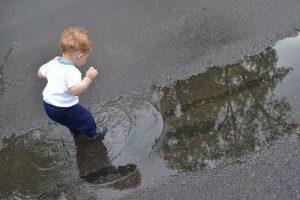 niño pelirrojo saltando charco